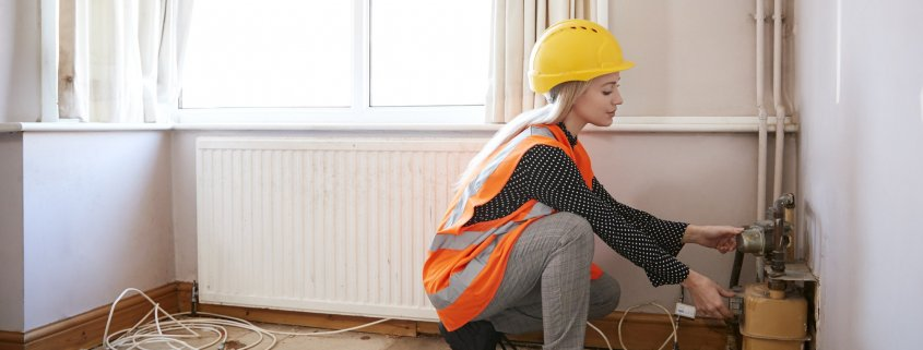 Female Surveyor In Hard Hat And High Visibility Jacket Checking Gas Supply