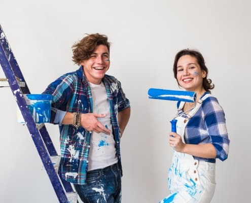 Renovation, repair and people concept - Young married couple painting walls in their new home
