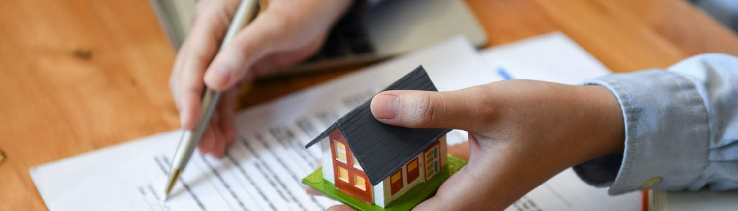 Brokers home sales hold pen and house model in hand.