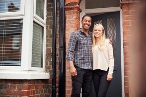 Portrait Of Proud Young Couple Standing Outside First Home Together
